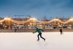 Active sorty male has fun in outdoor park on ice rink decorated with garlands, shows his talents of skating, makes fast movements. On skates, being confident royalty free stock photography