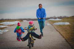 Active spor family- father on schooter with kids outside, little girl on bike royalty free stock photography