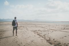 Active sport muscular bearded man standing on the sea shore at sunrise with backpack and looking horizon. Active sport muscular bearded man standing on the sea Royalty Free Stock Photography