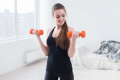 Active sportive athletic woman with dumbbells. Pumping up muscles biceps concept fitness sport training lifestyle Royalty Free Stock Photography
