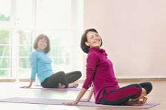 Active sportive mature women doing exercise in a gym. Active sportive women doing exercise in a gym. Two women doing stretching exercises and practicing yoga in royalty free stock images