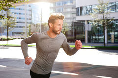 Active sports man running outside in the city. Portrait of an active sports man running outside in the city stock image