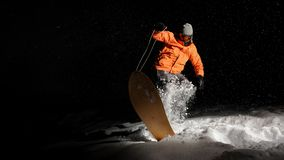 Active sportsman snowboarder in orange sportswear and mask jumping on a snowy hill at night. Active sportsman snowboarder dressed in orange sportswear and mask royalty free stock photo