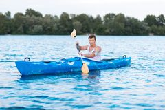 Strong active sportsman taking part in kayaking competition Stock Photos