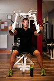 Active sportsman works out in fitness on butterfly machine Stock Images