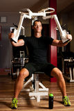 Active sportsman works out in fitness on butterfly machine Stock Photography
