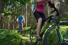 Active sporty couple riding mountain bikes on forest trail . stock image