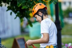 Active sporty kid in helmet doing activity in adventure park with all climbing equipment. Active children climb on the trees. And having fun outdoors. Summer royalty free stock images