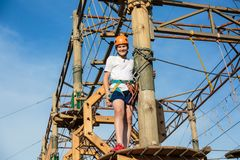 Active sporty kid in helmet doing activity in adventure park with all climbing equipment. Active children climb on the trees. And having fun outdoors. Summer stock photo