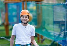 Active sporty kid in helmet doing activity in adventure park with all climbing equipment. Active children climb on the trees. And having fun outdoors. Summer royalty free stock photography