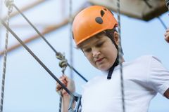 Active sporty kid in helmet doing activity in adventure park with all climbing equipment. Active children climb on the trees. And having fun outdoors. Summer royalty free stock photos