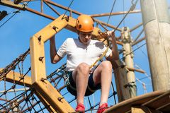 Active sporty kid in helmet doing activity in adventure park with all climbing equipment. Active children climb on the trees. And having fun outdoors. Summer stock images