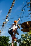 Active sporty kid in helmet doing activity in adventure park with all climbing equipment. Active children climb on the trees. And having fun outdoors. Summer stock image