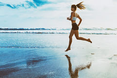Active sporty woman run along sunset ocean beach. Sports background. Active sporty woman run along ocean surf by water pool. Sunset sand beach background with stock images