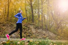 Active and sporty woman runner in autumn nature Royalty Free Stock Photography