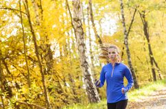 Active and sporty woman runner in autumn nature. Active and sporty woman runner is exercising in colorful autumn nature Stock Photo