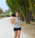 Active sporty young runner woman running in the park. Smiling runner athlete training outdoors Stock Images