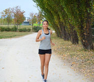 Active sporty young runner woman running in the park. Smiling runner athlete training outdoors Royalty Free Stock Photo