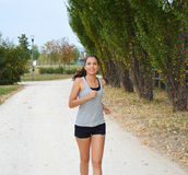 Active sporty young runner woman running in the park. Smiling runner athlete training outdoors Stock Image