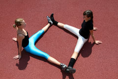 Active Stretching exercises. Two girls doing sport exercises royalty free stock photo