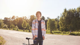 Active summer holidays. Portrait of young biker dessed in casual shirt looking seriously into camera enjoying ride outdoors by his. Bicycle. Teenager having Royalty Free Stock Images