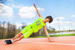 Active teenage boy holding a side plank outdoors Stock Images