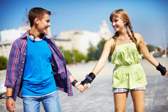 Active teens. Couple of two happy roller skaters looking at one another outside Stock Photos
