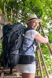 Active therapist with a backpack rises. On a wooden staircase to the mountain stock photos