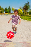 Active toddler. Active african american toddler kicking the ball royalty free stock photography