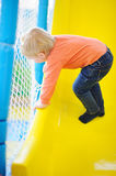 Active toddler boy playing at indoors playground Royalty Free Stock Image