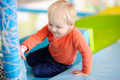 Active toddler boy playing at indoors playground Stock Image