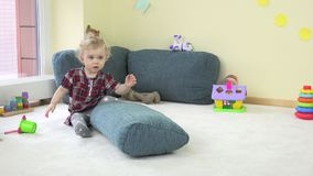 Active toddler girl climb on blue huge pillow and show true emotions at camera. stock video