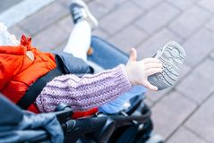 Active toddler girl enjoying her ride in a stroller. Close up of a toddler shoe. stock photo