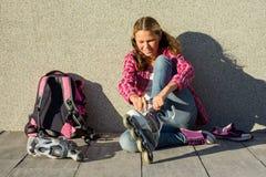 Active trägt jugendlich gir in den Viererkabelrollschuhen, städtischen Hintergrund zur Schau Lizenzfreie Stockfotos
