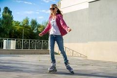 Active trägt jugendlich gir in den Viererkabelrollschuhen zur Schau Stockbild