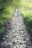 Active trip. Woman pushing the bike up hill Royalty Free Stock Photography