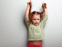 Active unhappy kid girl pulling her long hair on blue wall Stock Photo