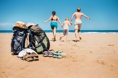 Active vacation concept image. Backpacker travelers family run t. O swim in ocean waves Stock Photography