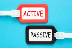 Active versus Passive. Written on luggage tags on blue background. Business concept royalty free stock photos