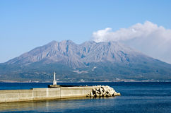 Active volcano with jetty. Active volcano and volcanic plume facing the sea called Sakurajima in Kagoshima, Japan Royalty Free Stock Photo