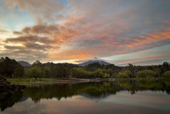 Active volcano Villarrica at morning sunrise reflection in lake Mallalafquén, Pucon, Chile. Two months after erupting the Villarrica volcano still is a risk stock photography