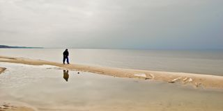 Active walk of an elderly man along the river bank. A person walks along the sandy shore, making a long walk on foot, admiring early spring and life stock photo
