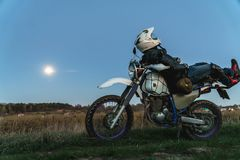 Active way of life, enduro motorcycle, a guy looks at the stars at night and the moon, unity with nature, the spirit of adventure stock photography