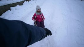 Active winter holiday, hand fast carries sled with joyful little girl on snowy road. Active winter holiday, father hand fast carries sled with joyful little girl stock footage