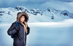 Active winter holidays in iceland. Happy beautiful woman with backpack traveling in the snowy mountains, trekking in the North Pole, extreme winter holidays royalty free stock photo