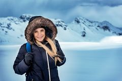 Active winter holidays. Portrait of a happy beautiful woman with backpack traveling in the snowy mountains, trekking in the North Pole, active winter holidays stock photography