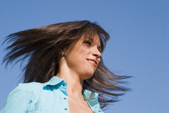 Active woman. Portrait of a young woman blowing her hair over the blue sky Stock Photo