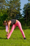Active woman. Young girl doing gymnastics in the nature with towel around neck Royalty Free Stock Images
