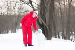 Active woman with adorable baby in snowy park Royalty Free Stock Photo