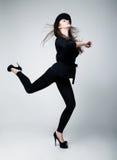 Active woman in black hat. Studio shot. Retro style  Fashion model girl in black running in studio Stock Photo